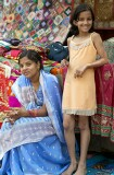 Mother and slightly glamourous young daughter selling their wares at the Janpath Lane textiles market, Delhi