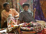 Two boys playing among the wares at the Janpath Lane textiles market, Delhi