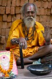 In a narrow street of Old Varanasi a Sadhu has set up on the pavement