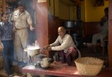 Everyday life in the narrow streets of old Varanasi: the old man has let his milk boil over but seems more amused than upset